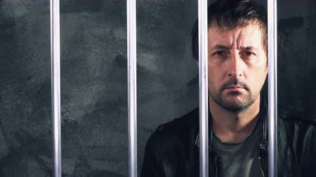 restraining : Depressed handcuffed man behind prison bars. Depressive arrested criminal male person imprisoned.
