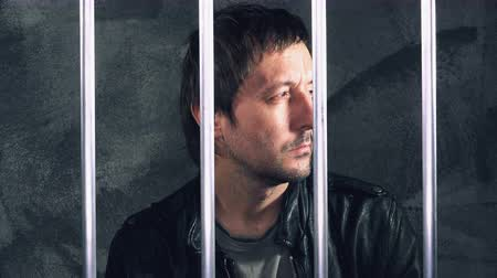 restraining : Pensive man behind prison bars. Arrested criminal male person imprisoned
