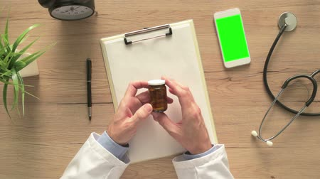 depressant : Overhead view of male doctor holding unlabeled bottle of various pills and medication, generic drugs concept, prescription medicine and healthcare Stock Footage