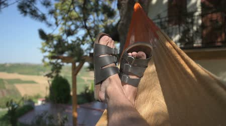 гамак : Man laying and relaxing in hammock, close up of relaxed male feet swinging in hammock in summer morning