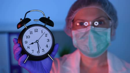 zdůraznit : Female surgeon medical specialist with clock emphasizing the importance of regular health care medical exams