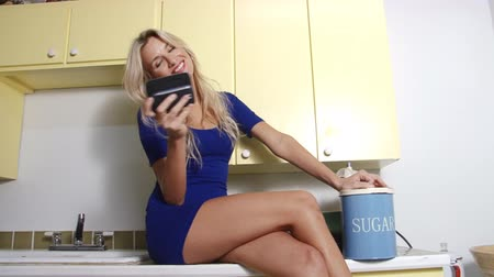 göğüs : Pretty blonde woman with mobile phone in kitchen Stok Video