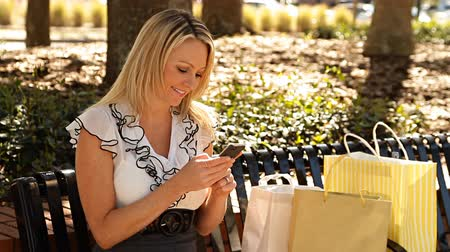 bolsa : Pretty consumer woman with smart phone and shopping bags outdoors