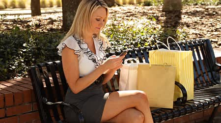 бизнес леди : Blonde woman taking a break from shopping using her mobile phone Стоковые видеозаписи