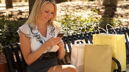 по телефону : Pretty consumer woman sending text on her mobile phone while sitting with shopping bags Стоковые видеозаписи