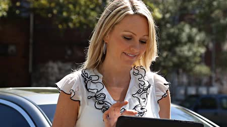 woman working : Pretty mature blonde woman with tablet computer by her car Stock Footage