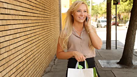 selektif : Happy young shopping woman on mobile phone outdoors