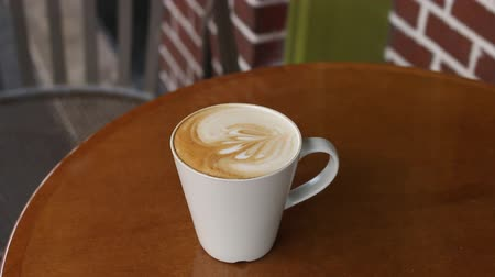 núpcias : Hand held shot of latte coffee drink on table at cafe Stock Footage