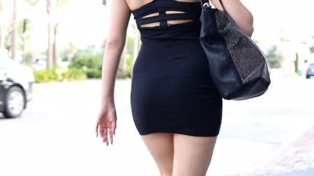 baixo ângulo : Sexy walk - woman walking in the city with tight black dress and purse