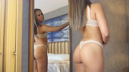 Sexy lingerie girl with fitness body in mirror admiring herself