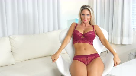 Sexy blonde lingerie woman in modern chair and positive Stok Video