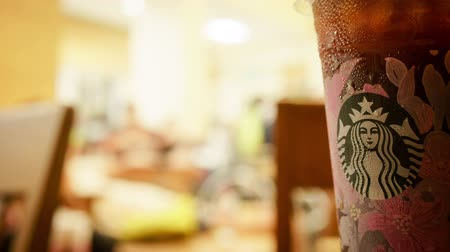 americano : BANGKOK, THAILAND- 28 February 2019 : Time lapse of Starbucks cold americano or black coffee in new Sakura cup and special blended coffee package for spring season
