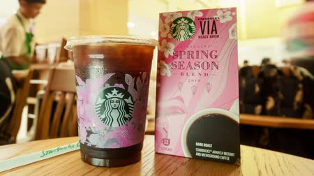 coffee shop : BANGKOK, THAILAND- 28 February 2019 : Time lapse of Starbucks cold americano or black coffee in new Sakura cup and special blended coffee package for spring season