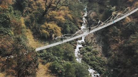 tourists cross the bridge in the mountains