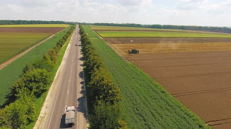 highway with cars near agricultural fields where there is harvesting