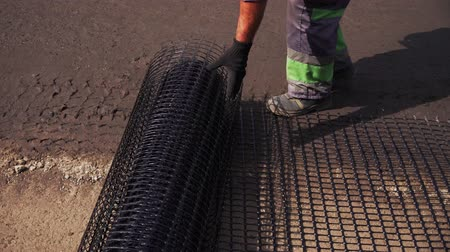 Worker rolls the mesh on the road before laying the asphalt Dostupné videozáznamy