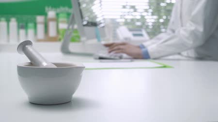 boticário : Professional pharmacist working with a computer and connecting online, mortar and pestle on the foreground: medicine and technology concept