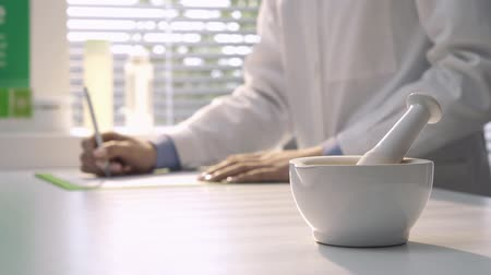 apotheker : Professional pharmacist working in the laboratory and writing prescription, mortar and pestle on the foreground, medicine and pharmacy concept Stockvideo