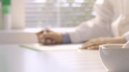 herbalist : Professional pharmacist working in the laboratory and writing prescription, mortar and pestle on the foreground, medicine and pharmacy concept Stock Footage