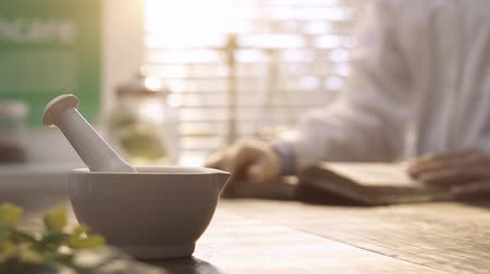 herbalist : Professional pharmacist working in the laboratory and reading a book on herbal medicine, mortar and pestle on the foreground Stock Footage