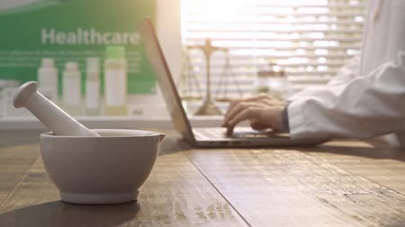 herbalist : Professional pharmacist working with a laptop and looking for medical preparations, mortar and pestle on the foreground: pharmacy and herbal medicine concept Stock Footage