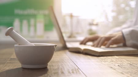 livraria : Professional pharmacist working with a laptop and looking for medical preparations, mortar and pestle on the foreground: pharmacy and herbal medicine concept Stock Footage