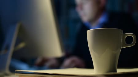 kifejező pozitivitás : Businessman working at night in the office, hot cup of coffee on the foreground