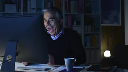kifejező pozitivitás : Cheerful successful businessman connecting online at night and receiving good news