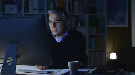 expressing negativity : Businessman working with his computer late at night and receiving bad news, he is desperate and screaming with head in hands Stock Footage