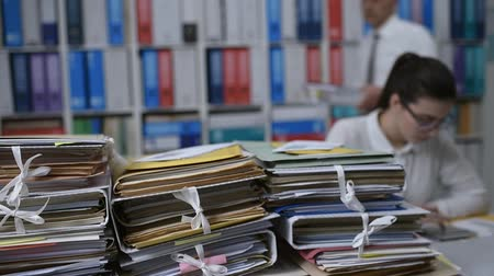 dosyalama : Piles of paperwork and files in the office, a businesswoman is working on the background