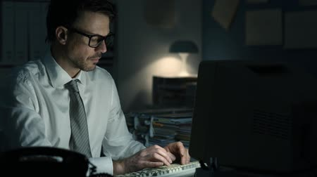 completo : Confident businessman working late at night, typing on keyboard and pressing return: he has completed his work and sends it on e-mail