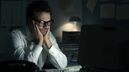 computer programmer : Tired frustrated business executive working at desk in the office, he is sitting at desk, staring at the computer screen and waiting