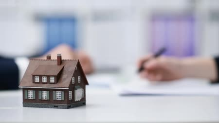 estate agency : Real estate agent and customer signing contract, the woman is buying a new home, model house in the foreground Stock Footage