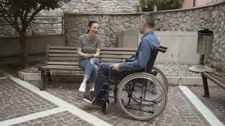 paraplegic : Man in wheelchair meeting his female friend outdoors and talking, handicap and relationships concept