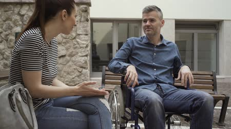 amado : Man in wheelchair meeting his female friend outdoors and talking, handicap and relationships concept