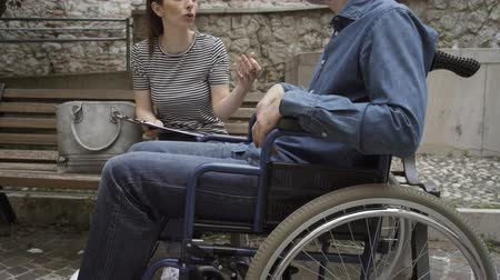 paraplegic : A social worker meeting with a clipboard, a handicap and assistance concept Stock Footage