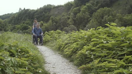 paraplegic : Young woman pushing a friend in wheelchair outdoors, they are visiting a natural park, accessibility and handicap concept Stock Footage