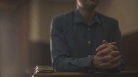 redemption : Devote man kneeling in the Church alone and praying, he is meditating with hands clasped: Christianity, religion and faith concept Stock Footage