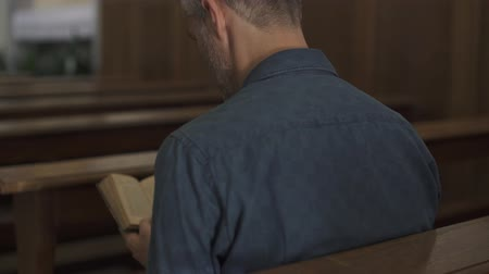 bible study : Devote Christian man praying in the Church and reading the Holy Bible, religion and spirituality concept