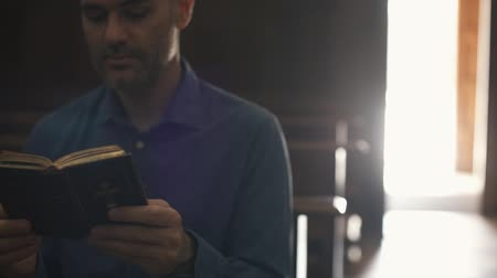 biblia : Devote Christian man praying in the Church and reading the Holy Bible, religion and spirituality concept