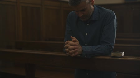 dua eden : Devote man kneeling in the Church alone and praying, he is meditating with hands clasped: Christianity, religion and faith concept Stok Video