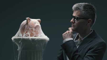 falido : Disappointed frustrated businessman blowing piggy bank with cobwebs: unsuccessful long term investment funds and frozen bank account concept Stock Footage