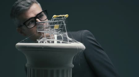 expressing negativity : Disappointed business executive blowing on a dusty miniature shopping cart with cobwebs: unsuccessful obsolete marketing strategies concept Stock Footage