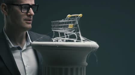 hayal kırıklığına uğramış : Disappointed business executive blowing on a dusty miniature shopping cart with cobwebs: unsuccessful obsolete marketing strategies concept Stok Video