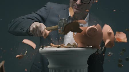 účty : Confident businessman breaking a piggy bank with a pile of coins: deposit funds, investments and savings concept