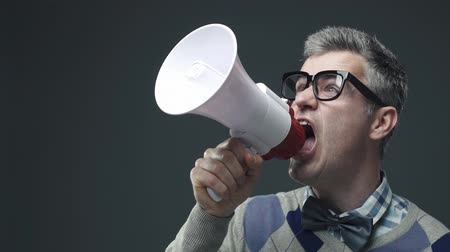 pateta : Nerd funny guy shouting an announcement message using a megaphone, marketing and communication concept