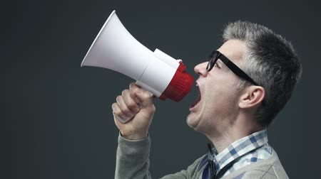 lelkesedés : Nerd funny guy shouting an announcement message using a megaphone, marketing and communication concept