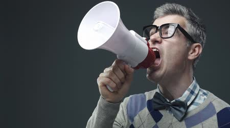 activist : Nerd funny guy shouting an announcement message using a megaphone, marketing and communication concept