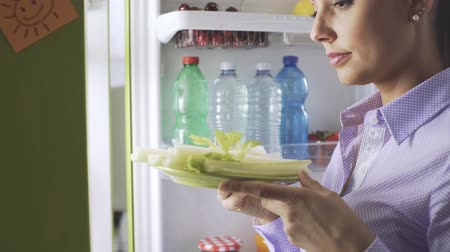 сельдерей : Young woman opening her fridge, she takes healthy food but then chooses to eat a delicious dessert