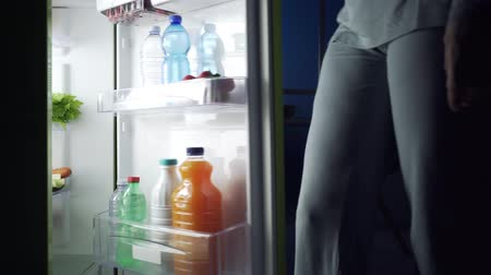 поздний завтрак : Woman taking a glass of milk from the fridge at night in the kitchen Стоковые видеозаписи